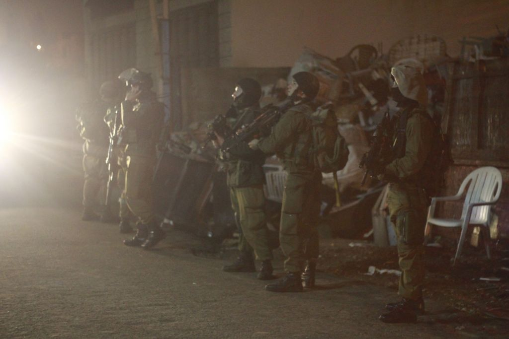 Soldiers set up a perimeter around the house of a suspect, to provide cover and ensure he doesn't escape. (Judah Ari Gross/Times of Israel)