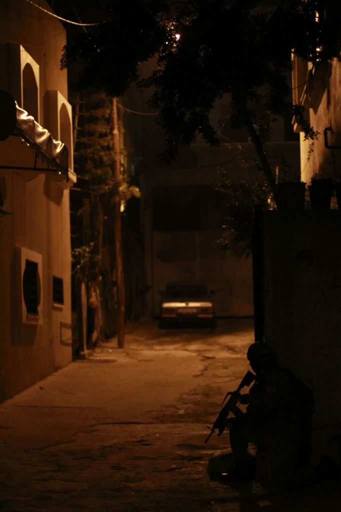 A soldier crouches in the shadows outside the home of a suspect in the Palestinian city of Qalqilya on January 14, 2016. Though the late-night arrests ordinarily occur without incident, IDF soldiers have been attacked by local residents who at times violently protest the arrest of suspects. (Judah Ari Gross/Times of Israel)