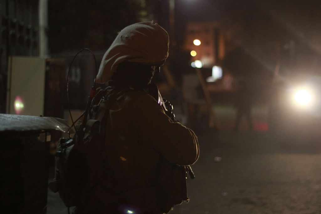 A soldier stands guard in the light of an army jeep in Qalqilya on January 14, 2016. The vehicles the army uses during these nighttime raids are all armored against bullets, rocks and Molotov cocktails. (Judah Ari Gross/Times of Israel)