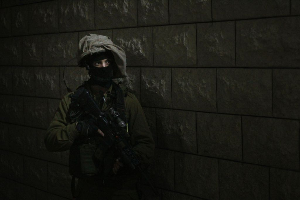 A soldier prepares to enter the home of a Palestinian teenager accused of throwing rocks at IDF troops during a riot in Qalqilya. An advance team had already entered the home to wake up the family, who initially denied that their son was home, on January 14, 2016. (Judah Ari Gross/Times of Israel)