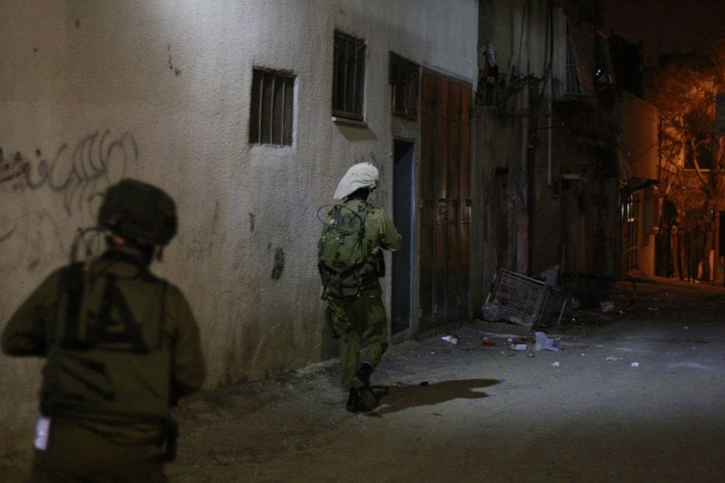 IDF soldiers move toward the home of two Palestinian teenagers who are believed to have taken part in violent protests in Qalqilya. An Arabic-speaking representative of the Defense Ministry's Coordinator of Government Activities in the Territories unit accompanies the battalion to facilitate conversation between the soldiers and the families of the accused on January 14, 2016. (Judah Ari Gross/Times of Israel)