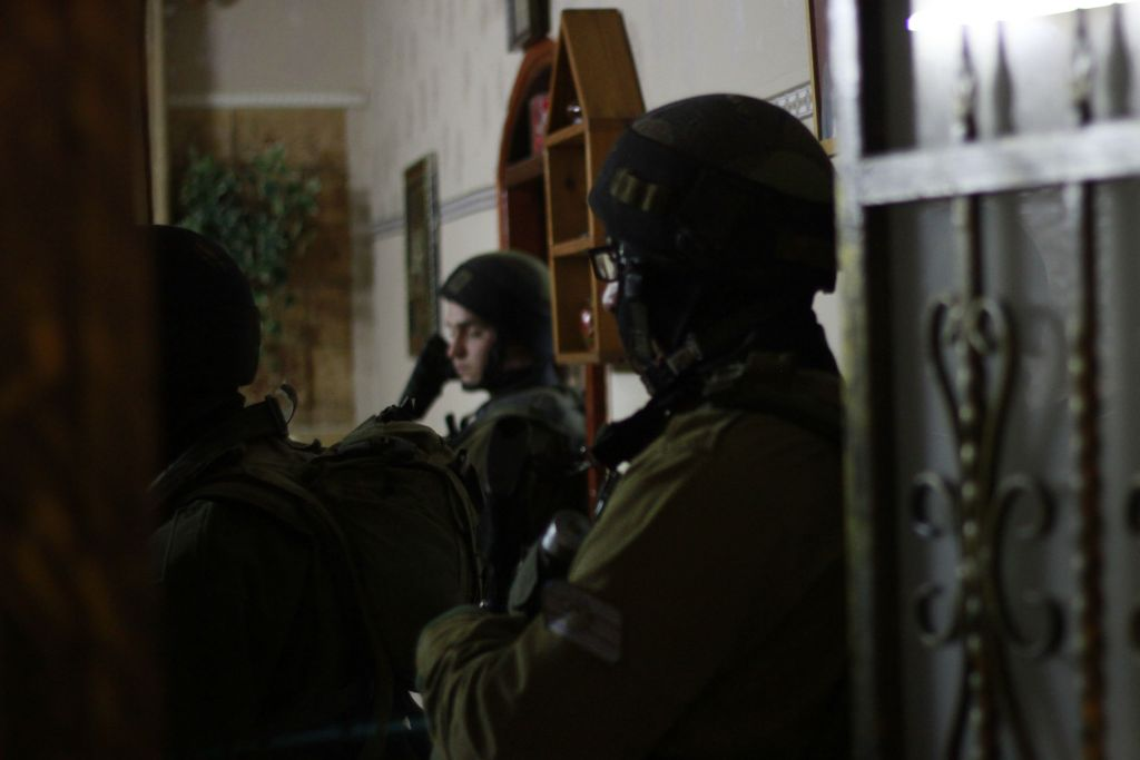 Soldiers stand in the doorway of a Palestinian family whose son is accused of throwing rocks at IDF troops in the West Bank city of Qalqilya on January 14, 2016. According to the soldiers' commander, Lt. Col. Nimrod Cibulski, their overall mission is to prevent the violence from spreading to the nearby settlement of Alfei Menashe or the city of Kfar Saba. (Judah Ari Gross/Times of Israel)
