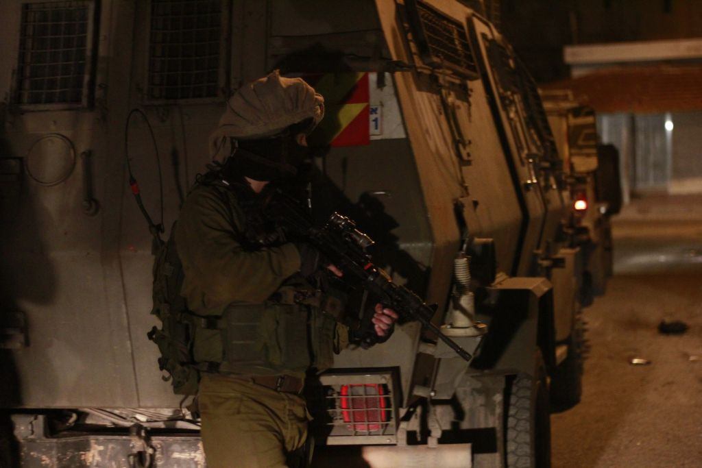A soldier stands guard outside of the Ze'ev, an armored vehicle, after a Palestinian teenager accused of throwing rocks at soldiers had been loaded into it in Qalqilya on January 14, 2016. The teenager's father led a group of soldiers to a nearby house where he said his son's ID was located. (Judah Ari Gross/Times of Israel)