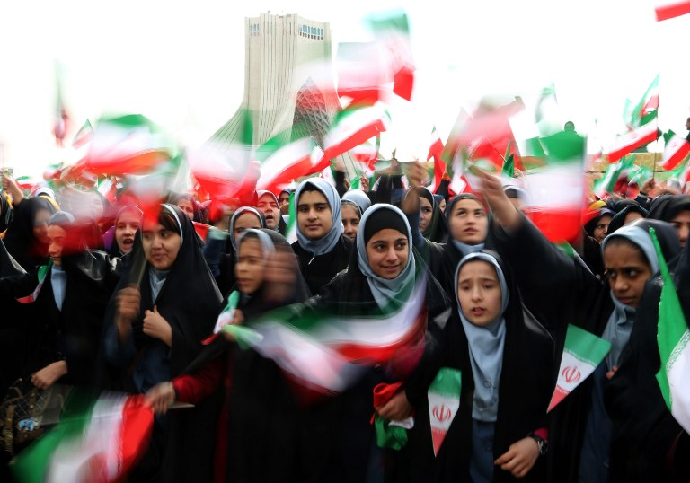 Iranian schoolgirls wave their national flag during celebrations in Tehran's Azadi Square (Freedom Square) to mark the 37th anniversary of the Islamic revolution on February 11, 2016. (Atta Kenare/AFP)