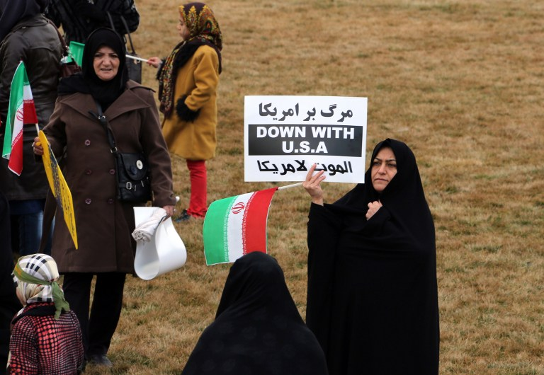 An Iranian woman holds an anti-US slogan during celebrations in Tehran's Azadi Square (Freedom Square) to mark the 37th anniversary of the Islamic revolution on February 11, 2016. (Atta Kenare/AFP)