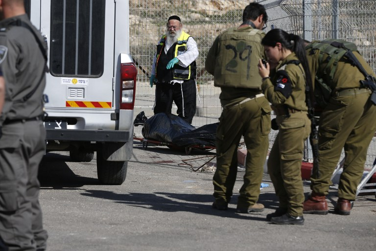 A Zaka volunteer and Israeli security forces stand next to the body of a Palestinian assailant shot dead following an attempt to stab border police at a checkpoint near Har Homa in the West Bank on February 14, 2016. (AFP/AHMAD GHARABLI)