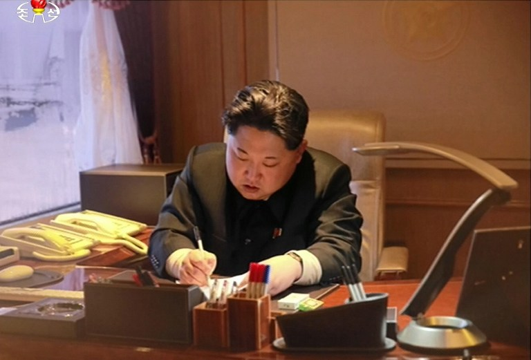 Illustrative photo of North Korean leader Kim Jong-Un signing on a document of earth observation satellite Kwangmyong 4 in Pyongyang, February 7, 2016 (AFP PHOTO / North Korean TV via YONHAP)