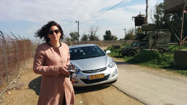 Yael Raz Lachyani stands inside the perimeter fence of Nahal Oz. Next to her are soldiers manning a monitoring device.