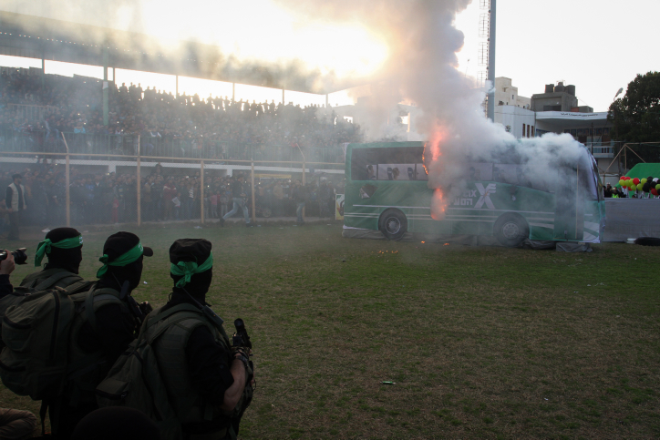 Palestinian militants of the Izz ad-Din al-Qassam, the armed wing of Hamas, burn a fake Israeli bus during an anti-Israel rally in the southern Gaza Strip city of Rafah on February 26, 2016. (Abed Rahim Khatib/Flash90)