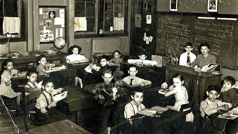In 1948, in school on the Lower East Side, Goldie sits with her back to the camera.