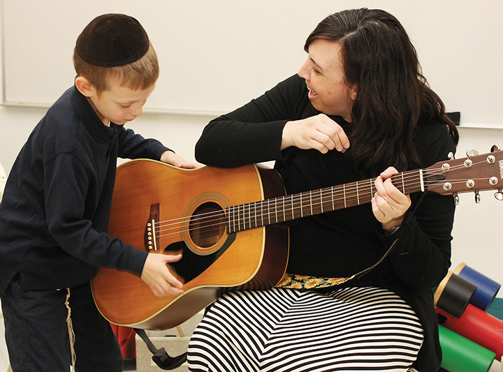 Erika Svolos shows how to make music with a guitar.