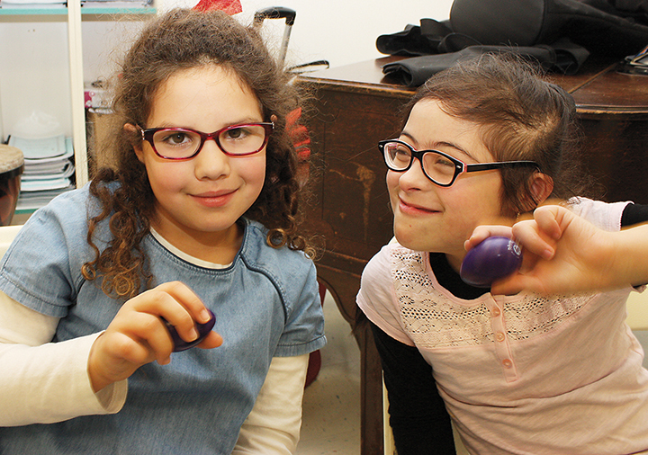 Students work with eggshakers, a type of musical instrument.