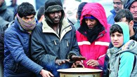"""Migrants warm their hands at """"the Jungle"""" camp in Calais"""