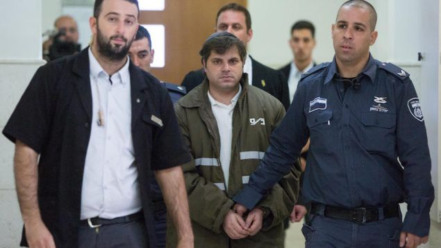 Police escorting Yosef Haim Ben-David, one of the three Jewish suspects in the murder of Mohammed Abu Khdeir. JTA