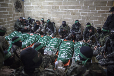 Palestinian fighters from the Izz ad-Din al-Qassam Brigades pray near the bodies of seven colleagues killed while repairing a tunnel, during their funeral at a mosque in Gaza City, on January 29, 2016. Photo by Emad Nassar/Flash90