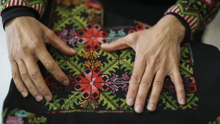 In this illustrative photo, a Bedouin woman shows crafts created by women at 'Desert Embroidery: Association for the Improvement of the Woman,' in the Bedouin city of Lakiya, on April 1, 2014. (Hadas Parush/Flash 90)