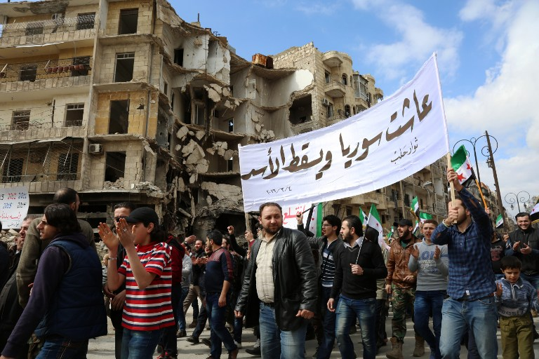 Syrian civilians and activists wave pre-Baath Syrian flags, now used by the Syrian opposition, during an anti-regime demonstration in the rebel-controlled side of Aleppo, on March 4, 2016. (AFP/KARAM AL-MASRI)