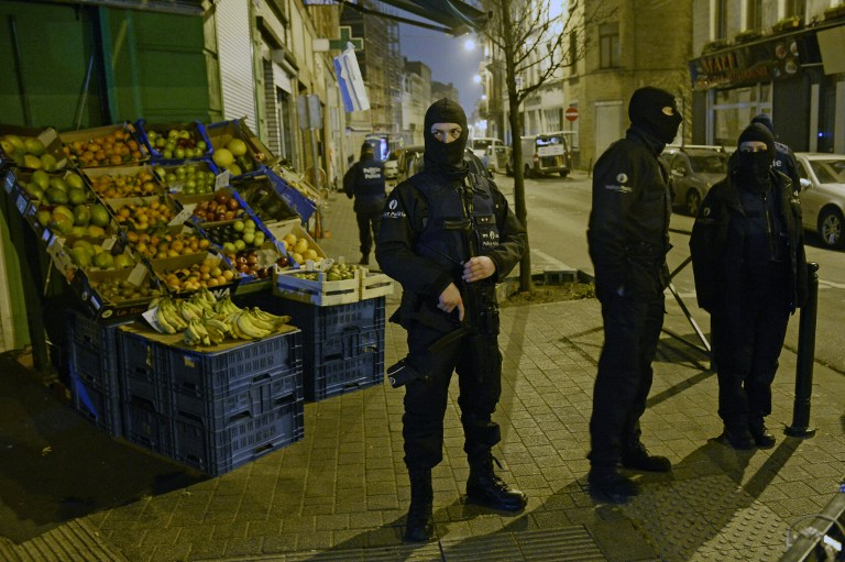Police stand guard near a scene of a police operation in the Molenbeek-Saint-Jean district in Brussels, on March 18, 2016, as part of the investigation into the Paris November attacks. (AFP / BELGA / DIRK WAEM)