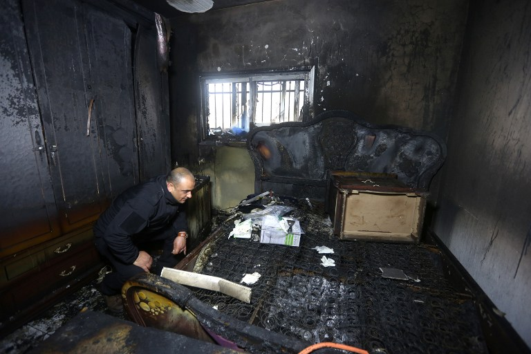A Palestinian police member inspects the damage inside a burned-out house belonging to a key witness to an arson attack last year by Jewish extremists that killed a Palestinian family, in the West Bank village of Duma, after fire broke out in the home in the early hours of July 31, 2015. (AFP/Jaafar Ashtiyeh)