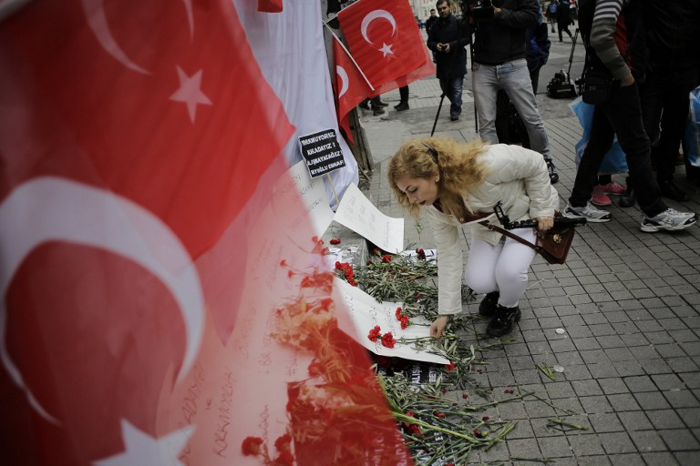 A woman lays flowers on a makeshift memorial at the location of the blast of a suicide attack on Istiklal Street, a major shopping and tourist district, in central Istanbul, on March 20, 2016. (AFP / YASIN AKGUL)
