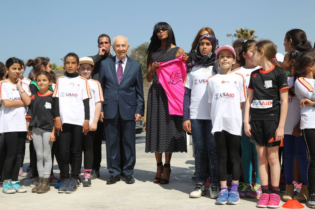 Supermodel Naomi Campbell being presented with a soccer jersey by one of the girls coexistence soccer teams sponsored by the Peres Center (Courtesy Rafi Delouya)