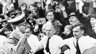 An Associated Press photograph shows Adolf Hitler, German Reichsfuehrer, acknowledging the ecstatic cheers of Sudeten Germans, as he entered Asch, on the heels of German armies which took over the ceded Czechoslovakian territory, on Oct. 3, 1938. The AP caption notes: 'Party members grip each other's belt, straining to hold the enthusiastic crowds in check.' (AP Photo)