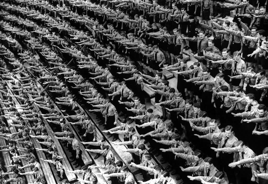 An Associated Press photograph shows some of over 132,000 members of the Hitler youth organisation assembled at the Olympic Stadium in Berlin, where German Chancellor Adolf Hitler and Dr. Joseph Goebbels addressed them, as part of the usual round of May Day festivities and demonstrations in Germany on May 1, 1939. The AP caption notes: 'The Fuhrer arrives and the members of the Hitler youth organisation rise as one man to give the Nazi salute at the demonstration in the Olympic Stadium, Berlin.' (AP Photo)