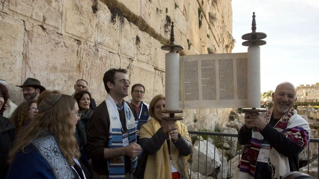 In this photo taken Thursday, Feb. 25, 2016, American Reform Rabbi, Zachary Shapiro, center left, and other American and Israeli Reform rabbis pray in the Western Wall, the holiest site where Jews can pray in Jerusalem's old city. (AP Photo/Sebastian Scheiner)