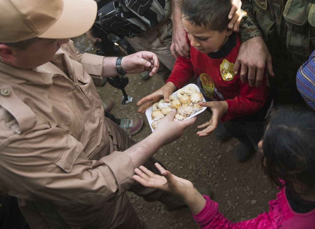 In this photo taken on Wednesday, March 2, 2016, children reach out for sweets distributed by Russian military in Maarzaf, about 15 kilometers west of Hama, Syria. Associated Press spent five days traveling through the port of Latakia and the surrounding areas in Syria during the cease-fire. (AP Photo/Pavel Golovkin)
