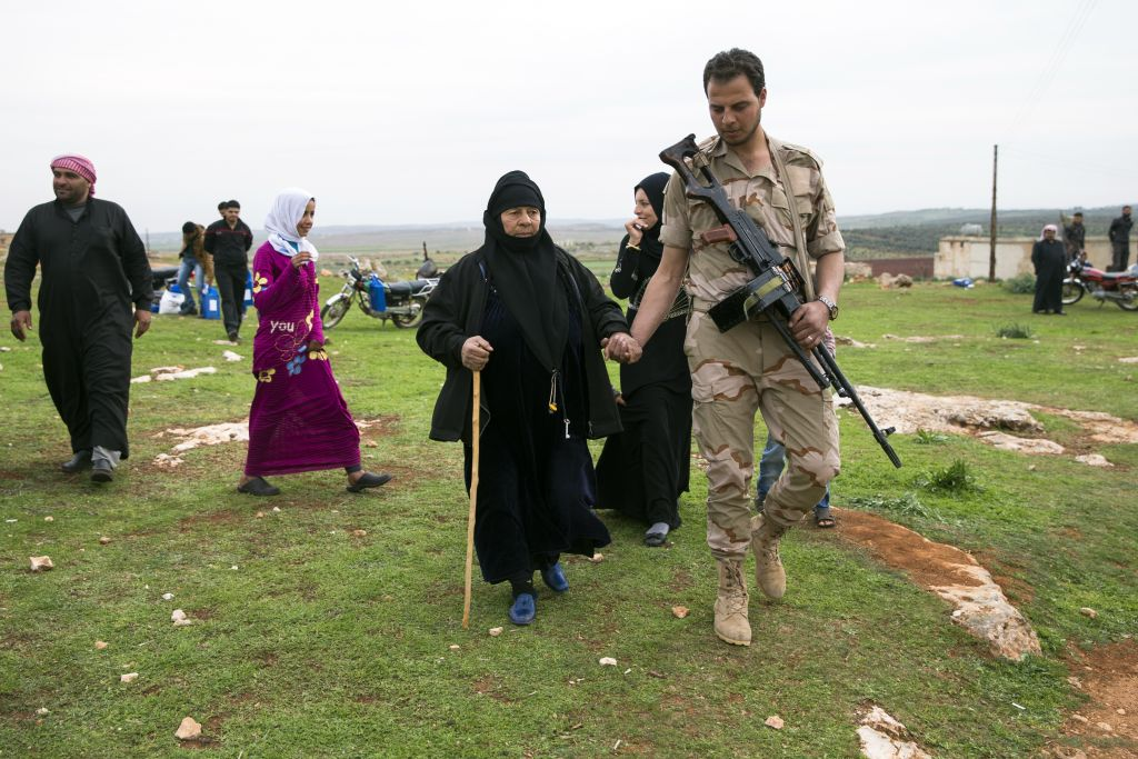 In this photo taken on Wednesday, March 2, 2016, a Syrian solder helps an elderly woman as she comes to receive humanitarian aid from Russian military near Maarzaf, about 15 kilometers west of Hama, Syria. Associated Press spent five days traveling through the port of Latakia and the surrounding areas in Syria during the cease-fire. (AP Photo/Pavel Golovkin)