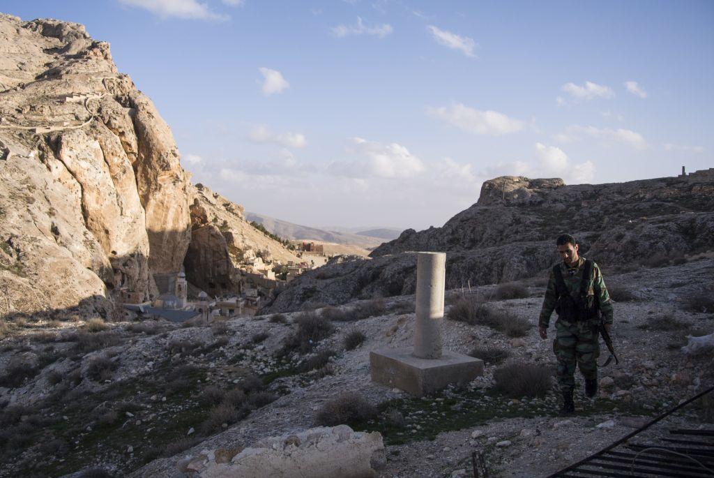 In this photo taken on Thursday, March 3, 2016, a Syrian solder walks, with the Greek Orthodox Mar Taqla monastery left in the background, in Maaloula, an ancient Christian town 60 kilometers (40 miles) northeast of Damascus, Syria. Associated Press spent five days traveling through the port of Latakia and the surrounding areas in Syria during the cease-fire. (AP Photo/Vladimir Isachenkov)