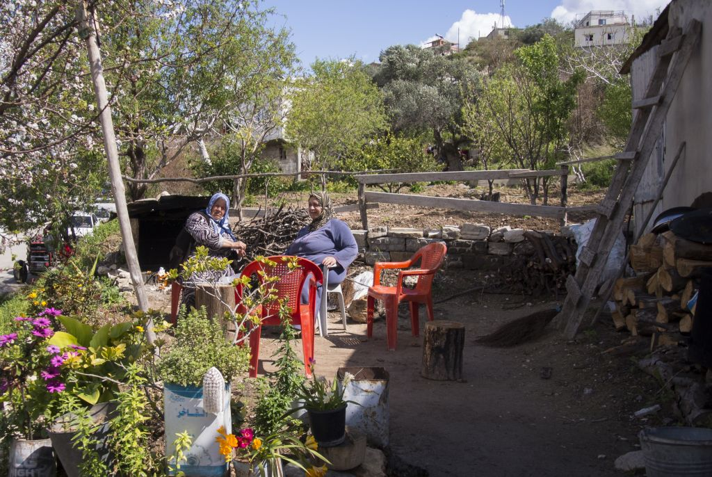 In this photo taken on Friday, March 4, 2016, elderly women sit in a yard in the village of Al-Issawiyah, about 15 kilometers south of the border with Turkey, Syria. Associated Press spent five days traveling through the port of Latakia and the surrounding areas in Syria during the cease-fire. (AP Photo/Vladimir Isachenkov)