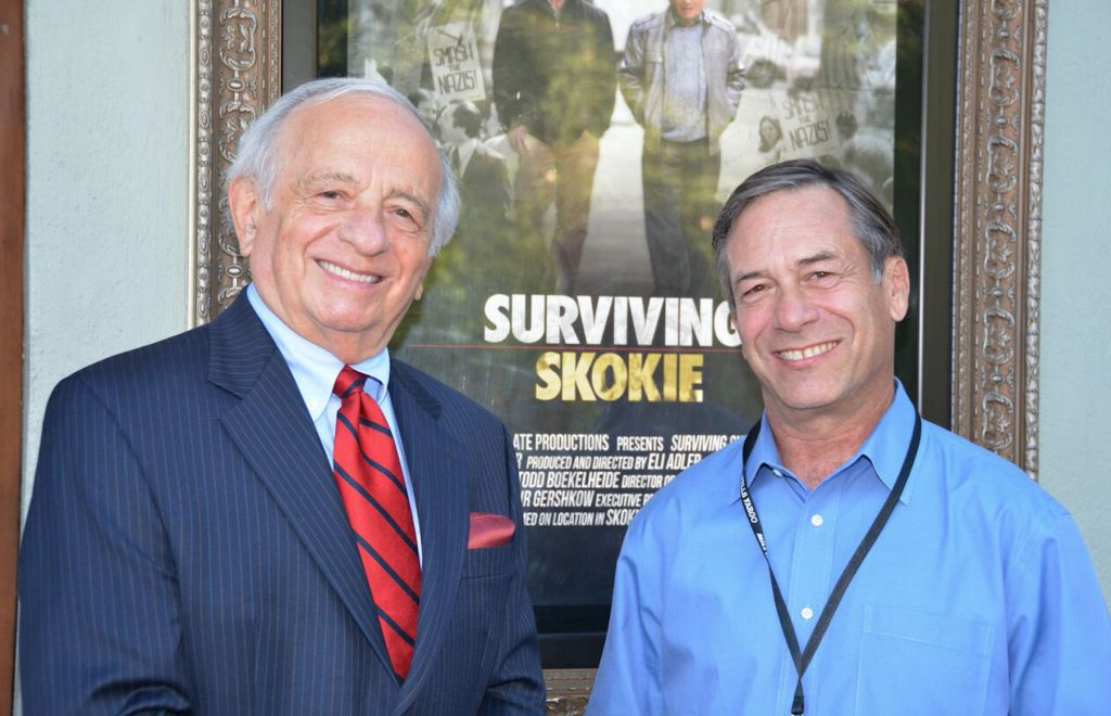 Jack Adler and son Eli stand in front of a movie poster for their documentary, 'Surviving Skokie.' (courtesy)