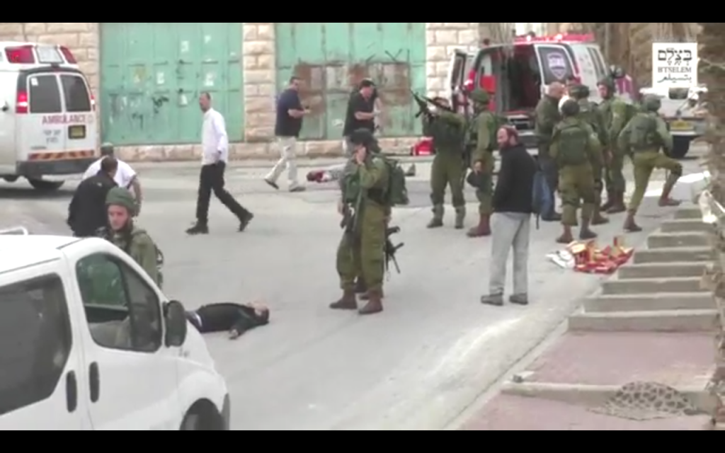 An IDF soldier loading his weapon before he appears to shoot an apparently unarmed, prone Palestinian assailant in the head following a stabbing attack in Hebron on March 24, 2016. (Screen capture: B'Tselem)