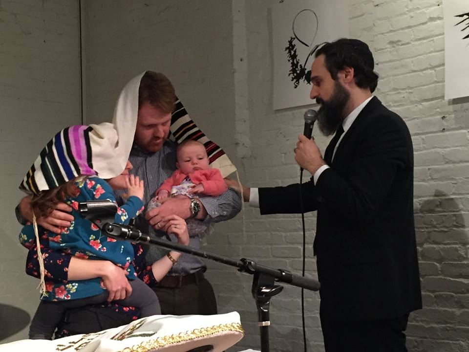 Rabbi Dan Ain blessing a young family. 'If I can inspire the parents and the children can see their parents inspired that will make all the difference.' (Gina Schmeling)