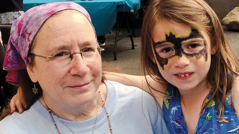 Siobhan Barry-Bratcher and her granddaughter, Alice, in Batgirl face paint at the United Synagogue of Hoboken's centennial celebration block party last May. (KIMBERLEE PIPER)