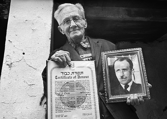 Edip Pilku with a picture of his father, Njazi, who protected the Neumanns during the war. (Norman H. Gorshman)