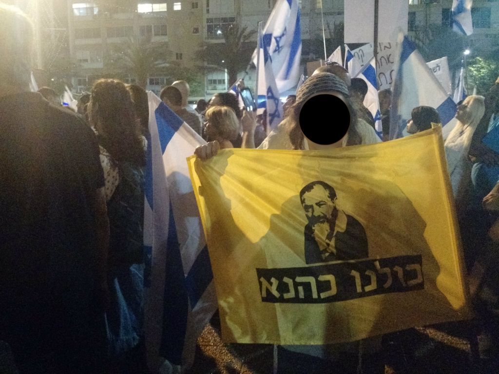 "A teen holds up a flag which reads ""We are all Kahane"" at a protest in support of a soldier charged with manslaughter in Tel Aviv's Rabin Square on April 19, 2016. (Judah Ari Gross/Times of Israel staff)"