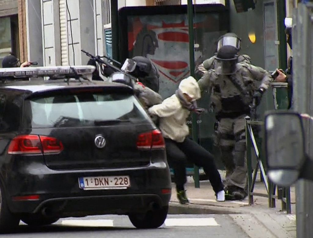 Screen capture from VTM shows Salah Abdeslam, center, as he is arrested by police and bundled into a police vehicle during a raid in the Molenbeek neighborhood of Brussels, Belgium, March 18, 2016. (VTM via AP)