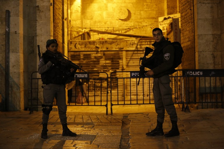 Israeli border policemen stand guard outside at Damascus Gate a main entrance to Jerusalem's Old City late
