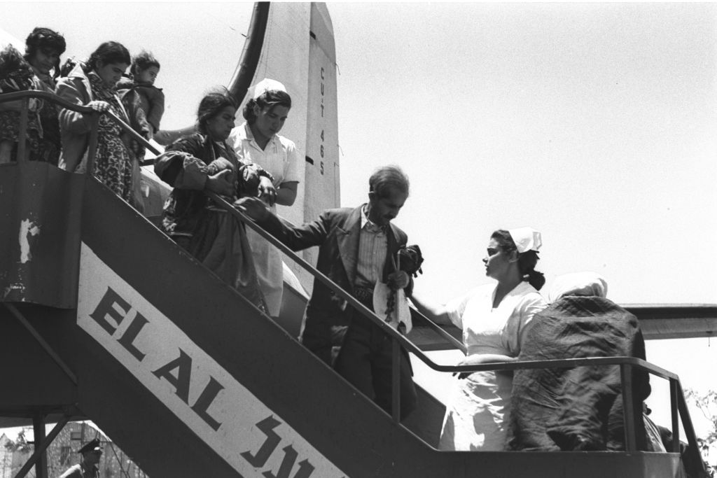 Immigrants from Iraq and Kurdistan exit their plane on arrival in Israel, having flown via Tehran, late spring 1951. Planes were arriving several times a day in this period, according to the original Government Press Office photo captions (Teddy Brauner, GPO)