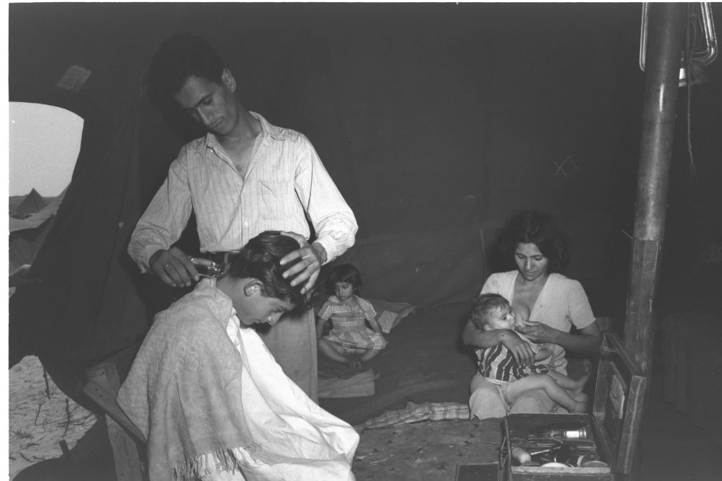 Barber Rachamim Azar, a new immigrant from Baghdad, carries out his trade in the tent he shares with his wife and two children at a maabara (immigrant camp) in central Israel in summer 1951. He told a Government Press Office photographer that he intended to move to a kibbutz (Teddy Brauner, GPO)