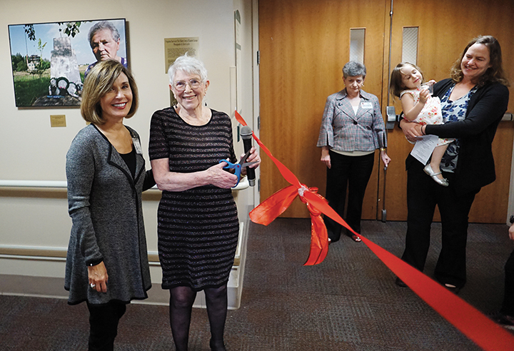Doris Levin cuts the ribbon to open the exhibit as the Jewish Home Family's president and CEO, Carol Silver Elliott, looks on.