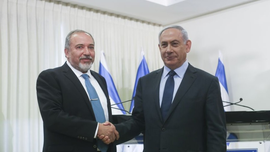 Prime Minister Benjamin Netanyahu and Yisrael Beytenu party leader Avigdor Liberman shake hands after signing a coalition agreement in the Knesset on Wednesday