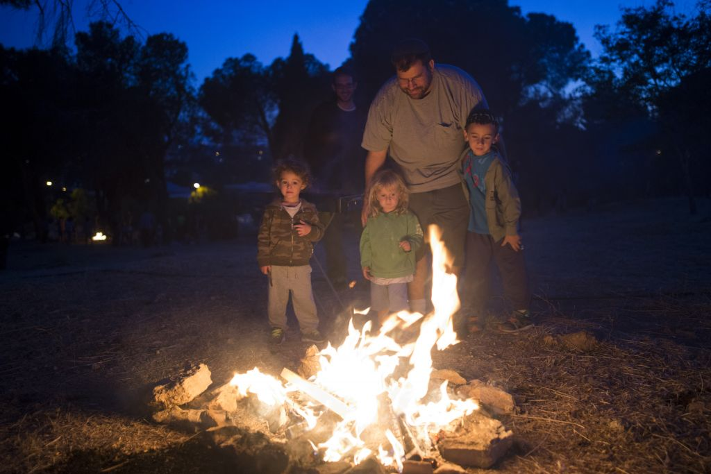 Israelis seen near a bonfire during celebrations of the Jewish holiday of Lag B'Omer in Jerusalem on May 25, 2016 (Yonatan Sindel/Flash90)