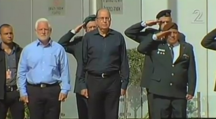 Outgoing Defense Minister Moshe Ya'alon stands with IDF top brass during a departure ceremony at the Kiyra military compound in Tel Aviv on May 22, 2016 (screen capture: Channel 2)