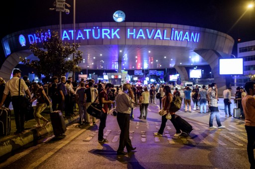 People stand outside the entrance after a terror attack at Turkey's Ataturk airport in Istanbul, June 28, 2016. (AFP/OZAN KOSE)