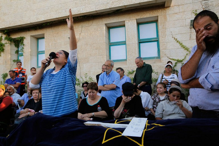 Rina Ariel, mourns over the body of her daughter Hallel, a 13-year-old girl who was fatally stabbed by a Palestinian terrorist in her home, during her funeral in the Kiryat Arba settlement on June 30, 2016. (AFP/Gil Cohen-Magen)
