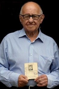 Holocaust survivor Zigi Shipper holds his entry passport from 1946 at his home