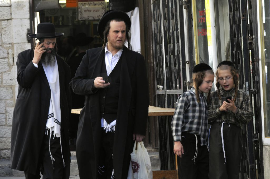 Ultra-Orthodox Jews on the phone in Mea Shearim in Jerusalem (Serge Attal / FLASH90